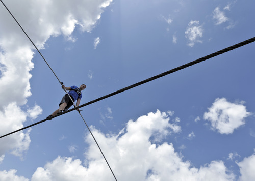 High wire performer Nik Wallenda walks across a wire as he practices Tuesday, June 18, 2013 in Sarasota, Fla.  Wallenda, a seventh generation high-wire walker, will attempt to walk across the Grand Canyon on Sunday, June 23, 2013.  (AP Photo/Chris O'Meara)