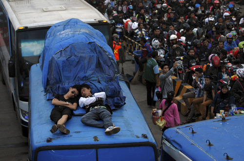 Indonesian men take a nap on the roof of a bus as they wait for their turn to board a ferry to cross to Sumatra island at a port in Merak, Indonesia, Sunday, Aug. 4, 2013. The mass exodus out of the capital and other major cities in the world's most populous Muslim country is underway as millions are heading home to their home towns to celebrate Eid al-Fitr holiday next week that marks the end of the holy fasting month of Ramadan. (AP Photo)