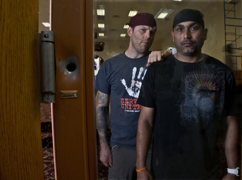 In this July 31, 2013, photo, Pardeep Kaleka, right, and Arno Michaelis pose for a photo at the Sikh Temple of Wisconsin in Oak Creek, Wis. At left is a bullet hole from a shooting at the temple a year ago when a white supremacist shot and killed six temple members, including Kaleka's father, Satwant Singh Kaleka. Michaelis, a former skinhead, reached out to Kaleka after the shooting and since then the pair have formed an unlikely alliance, teaming up to preach a message of peace throughout Milwaukee. (AP Photo/Morry Gash)