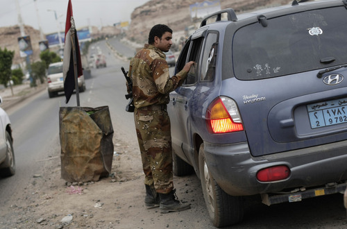 A Yemeni soldier inspects a car at a checkpoint on a street leading to the U.S. embassy in Sanaa, Yemen, Sunday, Aug. 4, 2013. Security forces close access roads, put up extra blast walls and beef up patrols near some of the 21 U.S. diplomatic missions in the Muslim world that Washington ordered closed for the weekend over a ``significant threat'' of an al-Qaida attack.  (AP Photo/Hani Mohammed)