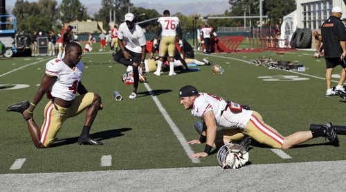 Newly-signed San Francisco 49ers wide receivers Austin Collie, right, and Lavelle Hawkins stretch during NFL football training camp on Friday, Aug. 2, 2013, in Santa Clara, Calif. (AP Photo/Marcio Jose Sanchez)