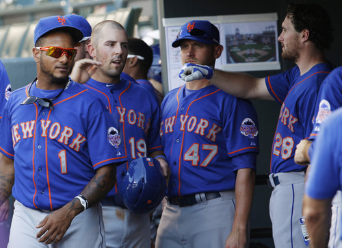 New York Mets' Zach Lutz, second from left, is congratulated by teammates Jordany Valdespin (1), Andrew Brown and Daniel Murphy (28) after Lutz scored on a force play against the Colorado Rockies in the fifth inning of a baseball game in Denver on Thursday, June 27, 2013. (AP Photo/David Zalubowski)