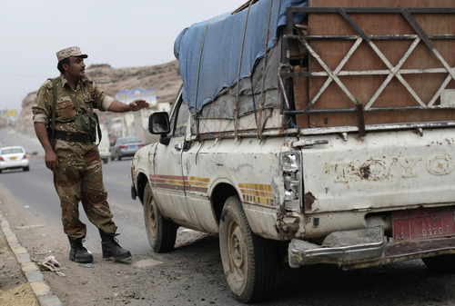 A Yemeni soldier stops a car at a checkpoint in a street leading to the U.S. embassy in Sanaa, Yemen, Sunday, Aug. 4, 2013. Security forces close access roads, put up extra blast walls and beef up patrols near some of the 21 U.S. diplomatic missions in the Muslim world that Washington ordered closed for the weekend over a ``significant threat'' of an al-Qaida attack.  (AP Photo/Hani Mohammed)