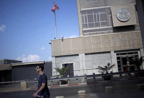 A ,man walks past the U.S Embassy in Tel Aviv, Israel, Sunday, Aug. 4, 2013. The threat of a terrorist attack led to the weekend closure of 21 U.S. embassies and consulates in the Muslim world and a global travel warning to Americans, the first such alert since an announcement before the 10th anniversary of the Sept. 11 strikes. (AP Photo/Ariel Schalit)