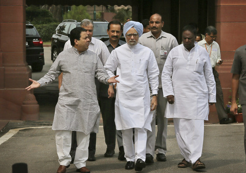 Indian Prime Minister Manmohan Singh, center, talks to his cabinet members as they walk towards media after his arrival at the opening day of the monsoon session of the parliament, in New Delhi, India, Monday, Aug. 5, 2013. Singh on Monday appealed to the Opposition to cooperate in smooth functioning of Parliament and said government is willing to discuss all issues during the Monsoon Session, according to local news reports. (AP Photo/Manish Swarup)