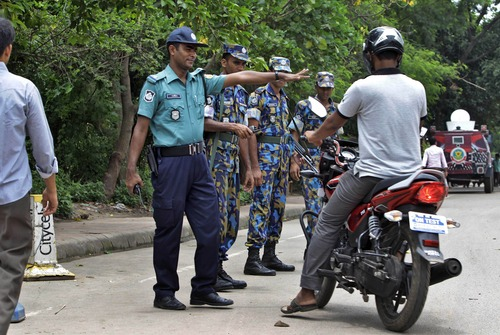 Bangladeshi police stop a motorist for checking in front of the U.S. embassy building that remained closed due to security threat in Dhaka, Bangladesh, Sunday, Aug. 4, 2013. The threat of a terrorist attack led to the weekend closure of 21 U.S. embassies and consulates in the Muslim world and a global travel warning to Americans, the first such alert since an announcement before the 10th anniversary of the Sept. 11 strikes. (AP Photo/A.M. Ahad)