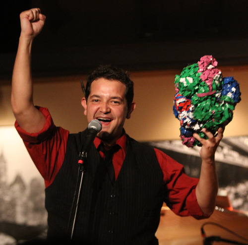 Rick Egan  | The Salt Lake Tribune   Matt Zumbrano congratulates the winning bidder as he auctions off a ball of tape, during the R.E.A.C.H. Cabaret at the Grind Coffee House in Cedar City, Friday, July 19, 2013.