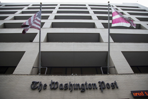 An American flag, left, and a District of Columbia fly outside the Washington Post building in Washington, Tuesday, Aug. 6, 2013. Amazon.com founder Jeff Bezos bought the Washington Post for $250 million. (AP Photo/Evan Vucci)