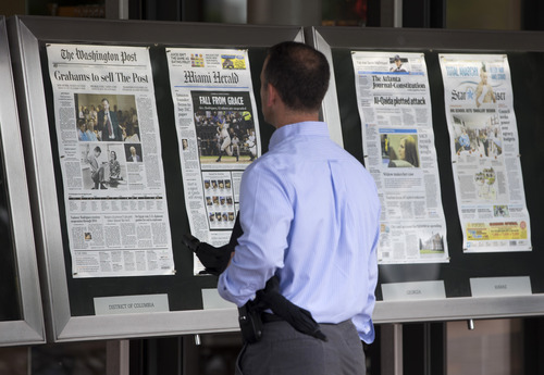 A visitor views the front page of the Washington Post, displayed outside the Newseum in Washington, Tuesday, Aug. 6, 2013, a day after it was announced tha Amazong.com founder Jeff Bezos bought the Washington Post for $250 million. (AP Photo/Evan Vucci)