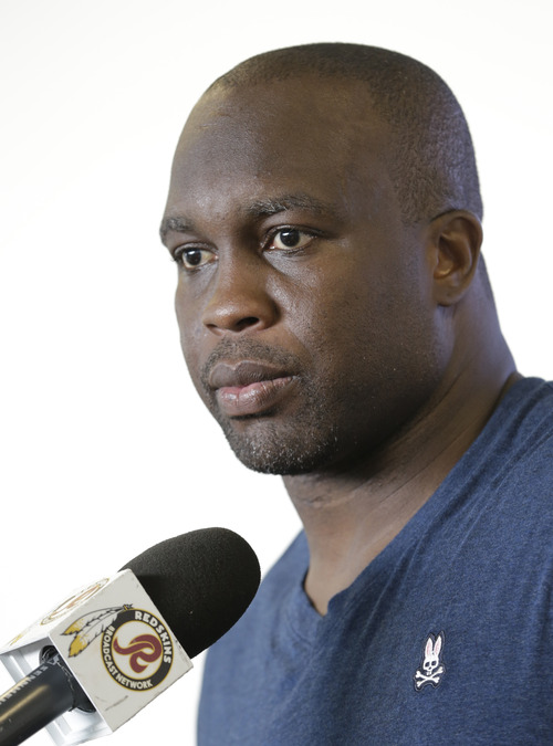 """FILE - In this July 24, 2013 file photo, Washington Redskins linebacker London Fletcher answers reporters questions during a news conference at the teams training facility in Richmond, Va. It's become routine to say that Fletcher has never missed a game in his NFL career. It's routine to hear him say that he's been """"blessed"""" with """"good genes."""" It's routine to hear him insist that he only thinks about his playing streak when reporters bring it up.  (AP Photo/Steve Helber, File)"""