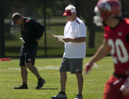 Steve Griffin | The Salt Lake Tribune Utah co-offensive coordinator, Dennis Erickson, center, looks at the play chart during football practice on the baseball field on the University of Utah campus in Salt Lake City, Utah Monday August 5, 2013.
