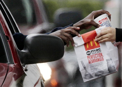 FILE - In this Jan. 22, 2010 file photo, a customer grabs lunch at a McDonalds drive-through in Chicago.  Fast-food chains such as McDonald's, Burger King and Wendy's are trumpeting pricier, premium offerings to shed their image as purveyors of greasy junk food and convince customers to spend a few extra bucks.(AP Photo/M. Spencer Green, File)