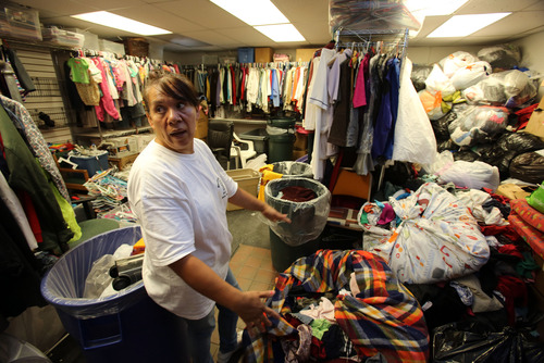 Francisco Kjolseth  |  The Salt Lake Tribune Elvira Garcia, a part-time worker at the Crossroads Urban Center Thrift Shop along Indiana Avenue in west Salt Lake City, looks over the donations that have come to be sorted. The center caters to a very diverse crowd representing many countries; shoes and clothes are the most sought-after items.
