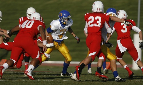 Chris Detrick  |  The Salt Lake Tribune Orem's Cole Payne (4) runs past East's Patrick Palau (40) and East's Zach Swenson (23) during a game at East High School in October 2011.