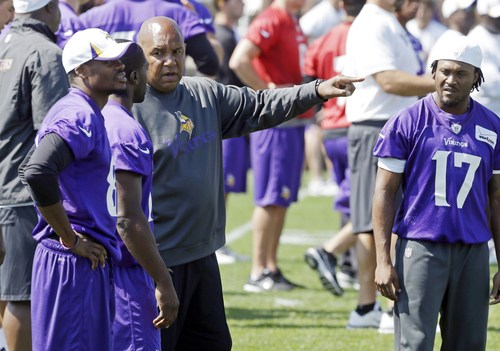 Minnesota Vikings wide receiver Jarius Wright, right  listens in as wide receiver coach George Stewart talks to wide receivers Jerome Simpson, left, and Greg Jennings during the NFL football training camp, Wednesday, Aug. 7, 2013 in Mankato, Minn. Stewart is being counted on to help a new look receiver corps get up to speed in training camp. (AP Photo/Jim Mone)