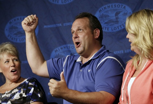 Paul White, of Ham Lake, Minn. accompanied by his girlfriend Kim VanReese, right, shouts during a news conference after he was announced one of the winners of the $448.4 million Powerball Jackpot, Thursday, Aug. 8, 2013 in Minneapolis. White's share of the jackpot is $149.4 million. The woman at left is a co-worker friend. (AP Photo/Jim Mone)