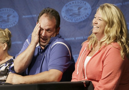 Paul White, of Ham Lake, Minn., gets a laugh from his girlfriend Kim VanReese, right, as he talks about his plans after he was announced one of the winners of the $448.4 million Powerball Jackpot, Thursday, Aug. 8, 2013 in Minneapolis. White's share of the jackpot is $149.4 million. The woman at left is a co-worker friend. (AP Photo/Jim Mone)
