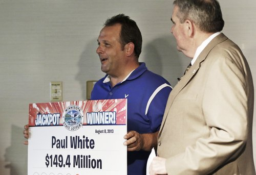Paul White, of Ham Lake, Minn. holds up his winning amount as Minnesota Lottery executive director Ed Van Petten, right, looks on during news conference after White was announced as one of the winners of the $448.4 million Powerball Jackpot, Thursday, Aug. 8, 2013 in Minneapolis. White's share of the jackpot is $149.4 million. The woman at left is a co-worker friend. (AP Photo/Jim Mone)