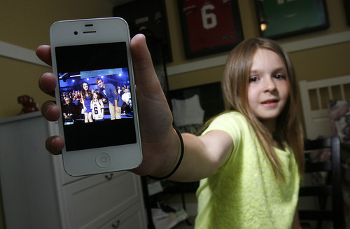 """Scott Sommerdorf      The Salt Lake Tribune Sam Gordon shows a photo her with two characters from the Disney Channel program """"Austin and Ally,"""" Wednesday, May 15, 2013."""