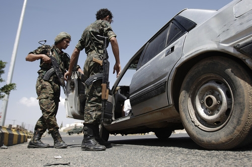 Yemeni soldiers inspect a car at a checkpoint on a street leading to the U.S. and British embassies in Sanaa, Yemen, Saturday, Aug. 10, 2013. Eighteen U.S. diplomatic outposts closed because of a terrorist threat will reopen Sunday, but the U.S. Embassy in Yemen will remain closed due to State Department ongoing concerns about potential terrorist attacks by al-Qaida in the Arabian Peninsula. (AP Photo/Hani Mohammed)