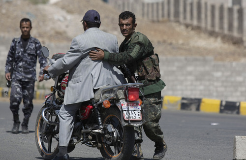 A Yemeni soldier searches a motorcyclist at a checkpoint on a street leading to the U.S. and British embassies in Sanaa, Yemen, Saturday, Aug. 10, 2013. Eighteen U.S. diplomatic outposts closed because of a terrorist threat will reopen Sunday, but the U.S. Embassy in Yemen will remain closed due to U.S. State Department ongoing concerns about potential terrorist attacks by al-Qaida in the Arabian Peninsula. (AP Photo/Hani Mohammed)