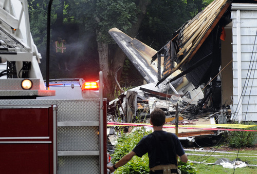 Fred Beckham     The Associated Press A firefighter surveys the scene of a small plane crash on Friday in East Haven, Conn. The multi-engine, propeller-driven plane plunged into a working-class suburban neighborhood near Tweed New Haven Airport, on Friday.