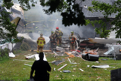 In this Friday, Aug. 9, 2013 photo, first responders work the scene of a small plane crash, in East Haven, Conn. A former Microsoft executive and his teenage son are presumed dead after their small plane crashed into a residential neighborhood a few blocks from an airport while trying to land, setting fire to two houses and killing as many as four other people, the man's brother and authorities said. (AP Photo/The New Haven Register, VM Williams)
