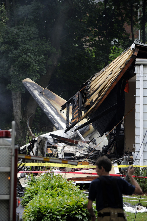A firefighter surveys the scene of a small plane crash Friday, Aug. 9, 2013, in East Haven, Conn. The multi-engine, propeller-driven plane plunged into a working-class suburban neighborhood near Tweed New Haven Airport, on Friday. (AP Photo/Fred Beckham)