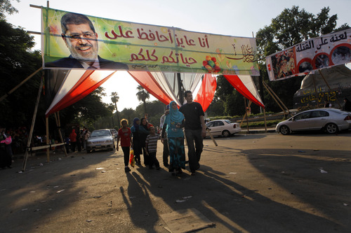 """Supporters of Egypt's ousted President Mohammed Morsi walk under his banner at Nahda Square, where protesters have installed their camp near Cairo University in Giza, southwest of Cairo, Egypt, Saturday, Aug. 10, 2013. Morsi supporters demanded his reinstatement, restoration of the suspended constitution drafted under Morsi and the return of the disbanded Islamist-dominated legislative council. The interim government rejected those demands, moving forward with a fast-track plan calling for revising the constitution and holding presidential and parliamentary elections early next year. The Arabic on the banner reads, """"I need to save all your lives."""" (AP Photo/Amr Nabil)"""