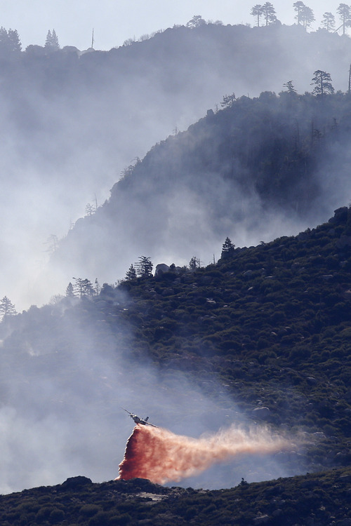 An air tanker drops fire retardant on a hot spot as firefighters continue to battle a wildfire on Friday, Aug. 9, 2013, near Banning, Calif. Southern California firefighters are facing another day of battle as they try to corral a wildfire that has destroyed 26 homes. Southern California's destructive wildfire has grown to 25 square miles, but containment has also increased. ((AP Photo/Jae C. Hong)