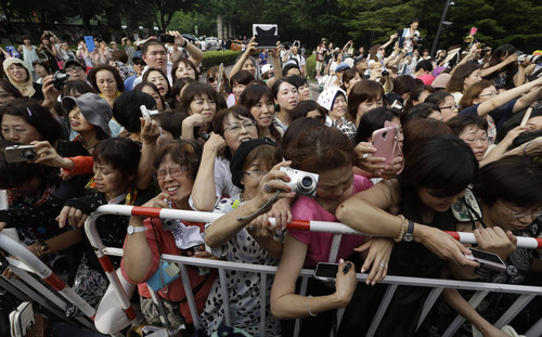 Asian fans go frenzies as they snap pictures of South Korean actor Lee Byung-hun, unseen, before his wedding ceremony with his bride and actress Rhee Min-jung in Seoul, South Korea, Saturday, Aug. 10, 2013. (AP Photo/Lee Jin-man)