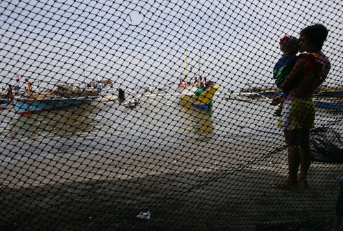 A mother and her child look at the idle fishing boats following an oil spill that reached the shores of Rosario township, Cavite province, south of Manila, Philippines Saturday Aug. 10, 2013. A large oil spill from an underwater pipe has contaminated waters in Manila Bay near the Philippine capital and prompted authorities on Friday to ban fishing. (AP Photo/Bullit Marquez)