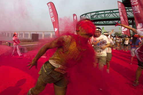 """Colored powder covers a runner's face as he runs through a """"color station"""" during a five-kilometer run in Beijing, China, Saturday, Aug. 10, 2013. Participants must go through dumps of colored powder at a """"color station"""" set up every kilometer in the race course. (AP Photo/Alexander F. Yuan)"""