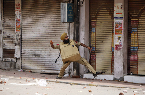 An Indian policeman throws stones at Hindus protesting against the state government after rival communities clashed in Kishtwar, in Jammu, India, Saturday, Aug. 10, 2013. Indian forces fired warning shots Saturday to enforce a curfew and to push angry people back into their homes in Kishtwar, in the Indian portion of Kashmir where clashes between Muslims and Hindus during Eid celebrations killed at least two people and injured another 24. (AP Photo/Channi Anand)