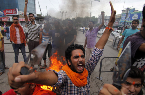 A Hindu protestor shouts slogans against the state government after rival communities clashed in Kishtwar, in Jammu, India, Saturday, Aug. 10, 2013. Indian forces fired warning shots Saturday to enforce a curfew and to push angry people back into their homes in Kishtwar, in the Indian portion of Kashmir where clashes between Muslims and Hindus during Eid celebrations killed at least two people and injured another 24. (AP Photo/Channi Anand)
