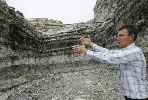 "Scott Sommerdorf   |  The Salt Lake Tribune Enefit mining engineer Ben France gestures towards the darker, ""mahogany zone"" of the oil shale deposit revealed in their ""box cut"" on their private holdings in eastern Uintah County, Wednesday, August 7, 2013. The Estonian state-owned company Enefit American Oil seeks to develop Utah oil shale."