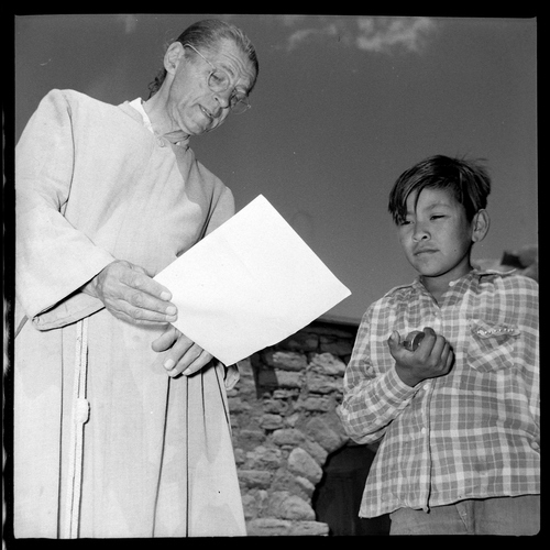 Salt Lake Tribune archive  Father Liebler talks to a young Navajo boy outside the school at St. Christopher's Mission in Bluff, Utah in 1950. St. Christopher's Episcopal Mission was established in 1943 when H. Baxter Liebler, an Episcopal priest from Old Greenwich, Conn., came to Bluff to establish a mission among the Navajo people. St. Christopher's is named after the patron saint of travelers. When Father Liebler arrived in Bluff, there were no missions, schools, or medical/hospital facilities for the Navajo living in this remote Utah section of the reservation. Before arriving in southeast Utah, Father  Liebler studied the Navajo language to make his message comprehensible to the Dineh and compatible with their understanding of harmony. He participated in Navajo ceremonies and wore his hair in the traditional Navajo style - long, pulled back and wrapped. A year after the mission was established, a school was started which became the only school for the 1,500 Navajo living in the central part of the Utah strip of the Navajo Reservation. A hospital/clinic building was completed in 1956. An estimated 500 babies were born in the clinic during the years it was in operation.