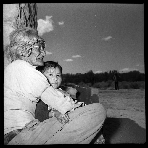 Salt Lake Tribune archive  An elderly Navajo woman holding a child at St. Christopher's Mission in Bluff, Utah, 1950. St. Christopher's Episcopal Mission was established in 1943 when H. Baxter Liebler, an Episcopal priest from Old Greenwich, Conn., came to Bluff to establish a mission among the Navajo people. St. Christopher's is named after the patron saint of travelers. When Father Liebler arrived in Bluff, there were no missions, schools, or medical/hospital facilities for the Navajo living in this remote Utah section of the reservation. Before arriving in southeast Utah, Father  Liebler studied the Navajo language to make his message comprehensible to the Dineh and compatible with their understanding of harmony. He participated in Navajo ceremonies and wore his hair in the traditional Navajo style - long, pulled back and wrapped. A year after the mission was established, a school was started which became the only school for the 1,500 Navajo living in the central part of the Utah strip of the Navajo Reservation. A hospital/clinic building was completed in 1956. An estimated 500 babies were born in the clinic during the years it was in operation.