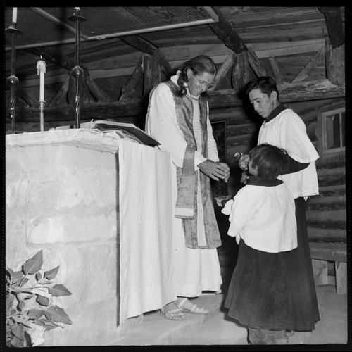 Salt Lake Tribune archive  Father Liebler holding church services at St. Christopher's Mission in Bluff, Utah in 1950. St. Christopher's Episcopal Mission was established in 1943 when H. Baxter Liebler, an Episcopal priest from Old Greenwich, Conn., came to Bluff to establish a mission among the Navajo people. St. Christopher's is named after the patron saint of travelers. When Father Liebler arrived in Bluff, there were no missions, schools, or medical/hospital facilities for the Navajo living in this remote Utah section of the reservation. Before arriving in southeast Utah, Father  Liebler studied the Navajo language to make his message comprehensible to the Dineh and compatible with their understanding of harmony. He participated in Navajo ceremonies and wore his hair in the traditional Navajo style - long, pulled back and wrapped. A year after the mission was established, a school was started which became the only school for the 1,500 Navajo living in the central part of the Utah strip of the Navajo Reservation. A hospital/clinic building was completed in 1956. An estimated 500 babies were born in the clinic during the years it was in operation.