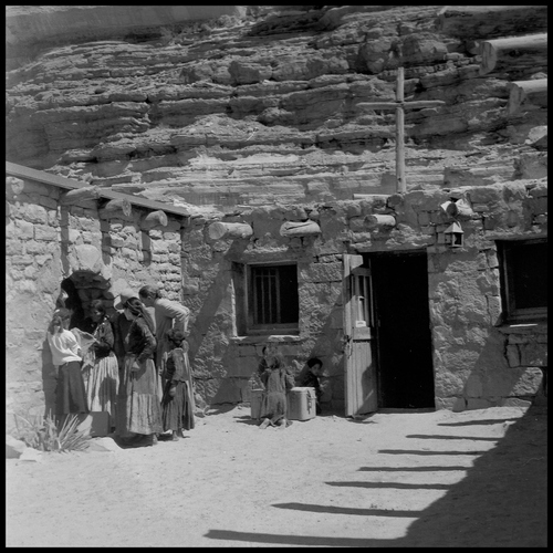 Salt Lake Tribune archive  Father Liebler talks to a group of people outside the chapel at St. Christopher's Mission in Bluff, Utah, 1950. St. Christopher's Episcopal Mission was established in 1943 when H. Baxter Liebler, an Episcopal priest from Old Greenwich, Conn., came to Bluff to establish a mission among the Navajo people. St. Christopher's is named after the patron saint of travelers. When Father Liebler arrived in Bluff, there were no missions, schools, or medical/hospital facilities for the Navajo living in this remote Utah section of the reservation. Before arriving in southeast Utah, Father  Liebler studied the Navajo language to make his message comprehensible to the Dineh and compatible with their understanding of harmony.  He participated in Navajo ceremonies and wore his hair in the traditional Navajo style - long, pulled back and wrapped. A year after the mission was established, a school was started which became the only school for the 1,500 Navajo living in the central part of the Utah strip of the Navajo Reservation. A hospital/clinic building was completed in 1956. An estimated 500 babies were born in the clinic during the years it was in operation.