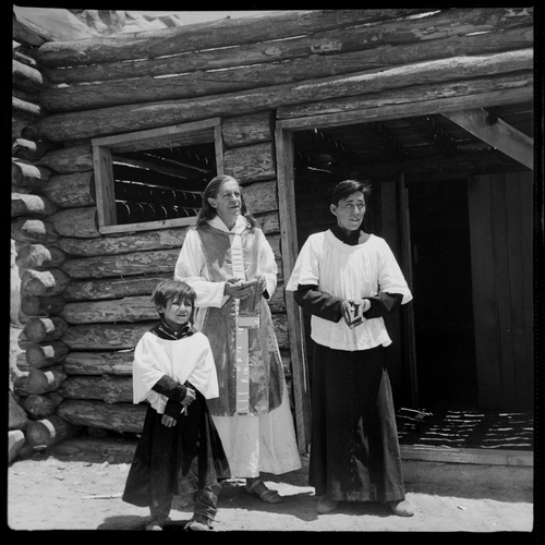 Salt Lake Tribune archive  Father Liebler and two Navajo boys prior to church services at St. Christopher's Mission in Bluff, Utah in 1950. St. Christopher's Episcopal Mission was established in 1943 when H. Baxter Liebler, an Episcopal priest from Old Greenwich, Conn., came to Bluff to establish a mission among the Navajo people. St. Christopher's is named after the patron saint of travelers. When Father Liebler arrived in Bluff, there were no missions, schools, or medical/hospital facilities for the Navajo living in this remote Utah section of the reservation. Before arriving in southeast Utah, Father  Liebler studied the Navajo language to make his message comprehensible to the Dineh and compatible with their understanding of harmony.  He participated in Navajo ceremonies and wore his hair in the traditional Navajo style - long, pulled back and wrapped. A year after the mission was established, a school was started which became the only school for the 1,500 Navajo living in the central part of the Utah strip of the Navajo Reservation. A hospital/clinic building was completed in 1956. An estimated 500 babies were born in the clinic during the years it was in operation.