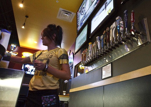 Leah Hogsten | The Salt Lake Tribune Bartender Nicona Stadtmueller works at the front bar of Buffalo Wild Wings, Layton where beers and mixed drinks are poured in a room behind her, Thursday, August 8, 2013. The beer pulls (at right) are non-functioning taps that alert customers to the varities of beer they serve. In 2012, Buffalo Wild Wings restaurant told liquor-control commissioners it would have to delay construction on its Layton store because the state had run out of liquor licenses. Since then, lawmakers have created more permits and now the chain has eight locations in Utah.