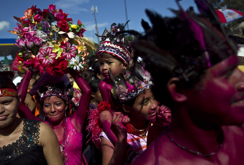 Devotees wearing indigenous costumes and with their bodies painted in red attend the festivities to honor Managua's patron saint Santo Domingo de Guzman in Managua, Nicaragua, Saturday, Aug. 10, 2013. The festival bring together devotees of all types of social and economic status including Catholics, transvestites, sex workers and gang members to one of the poorest neighborhoods of the capital city. (AP Photo/Esteban Felix)