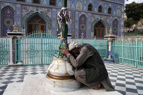 An Afghan Shiite man kisses the holy mace for blessings at the Karti Sakhi shrine in Kabul, Afghanistan, Monday, Aug. 12, 2013. Some Afghans who believe in Sufism, a mystical form of Islam, visit shrines everyday and offer prayers. (AP Photo/Rahmat Gul)