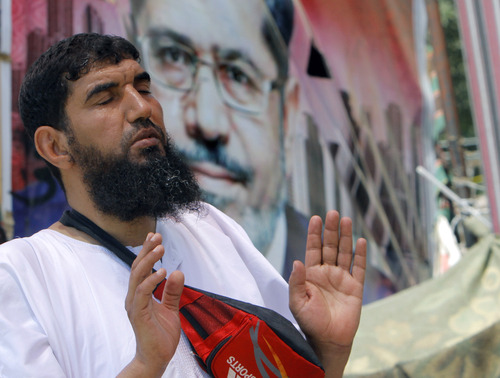 "A supporter of Egypt's ousted President Mohammed Morsi prays in front of his poster in Nahda Square, where protesters have installed their camp near Cairo University in Giza, southwestern Cairo, Egypt, Monday, Aug. 12, 2013. Egyptian authorities on Monday postponed a move to disperse two Cairo sit-ins by supporters of the country's ousted president to ""avoid bloodshed,"" an official said, as Islamist supporters stepped up rallies to demand his return to power. (AP Photo/Amr Nabil)"