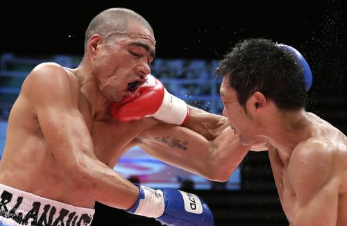 Japanese champion Akira Yaegashi, right, lands his right to challenger Oscar Blanquet of Mexico during their WBC flyweight world title boxing match in Tokyo, Monday, Aug. 12, 2013. Yaegashi won by a 3-0 decision. (AP Photo/Shizuo Kambayashi)