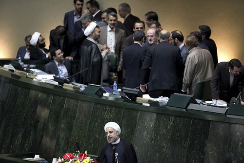 Iranian President Hasan Rouhani, below, stands at podium while lawmakers confer, above, in an open session of the parliament to debate on proposed Cabinet, in Tehran, Iran, Monday, Aug. 12, 2013. Hard-line Iranian lawmakers have challenged the new president's proposed Cabinet makeup, accusing him of nominating pro-Western figures and opposition supporters to ministerial posts. But President Hasan Rouhani told parliament on Monday that his government's priority will be to ease tensions with the outside world and improve the sanctions-battered economy. (AP Photo/Ebrahim Noroozi)