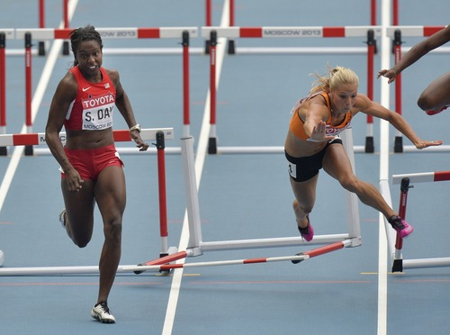 Netherlands' Nadine Broersen, right, falls as she runs beside United States' Sharon Day in the 100-mter hurdles of the heptathlon at the World Athletics Championships in the Luzhniki stadium in Moscow, Russia, Monday, Aug. 12, 2013. (AP Photo/Martin Meissner)