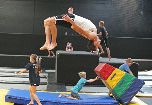 In this Wednesday, July 31, 2013 photo, Jacob Terrell, of Pleasantville, flips as others play at the Get Air Hang Time indoor trampoline park in Orem. Indoor trampoline parks have cropped up around the country in recent years, offering customers a chance to bounce, flip and jump in wall-to-wall trampolines. The jump gyms offer the kind of rain-or-shine suburban entertainment popular for birthday parties and summer camps. But some doctors and officials say the parks are dangerous and can cause serious injuries.  (AP Photo/Rick Bowmer)