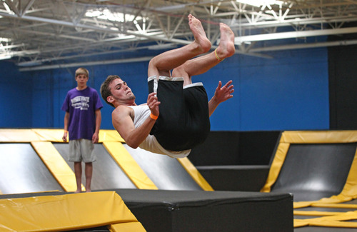 In this Wednesday, July 31, 2013, photo, Jacob Terrell of Pleasantville flips at the Get Air Hang Time indoor trampoline park in Orem. Indoor trampoline parks have cropped up around the country in recent years, offering customers a chance to bounce, flip and jump in wall-to-wall trampolines. The jump gyms offer the kind of rain-or-shine suburban entertainment popular for birthday parties and summer camps. But some doctors and officials say the parks are dangerous and can cause serious injuries.  (AP Photo/Rick Bowmer)